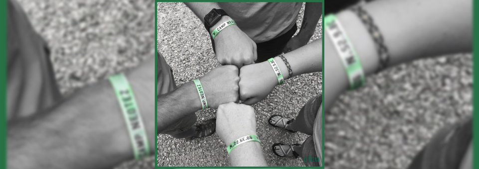 campers fist bump wearing bracelet with gps coordinates for Camp